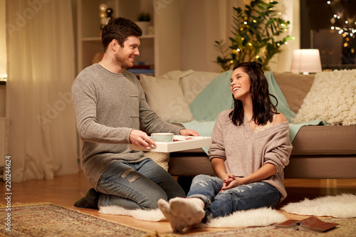 Poster leisure, hygge and people concept - happy couple with food on tray at home
