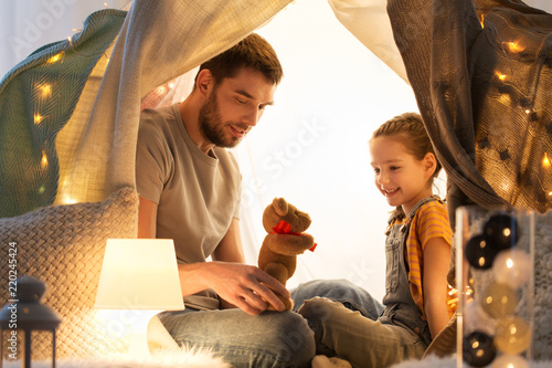 Leinwanddruck Bild family, hygge and people concept - happy father with teddy bear toy and little daughter playing in kids tent at night at home