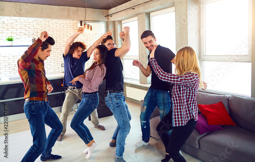 Friends dance fun at a student's party in the apartment. - 220247409