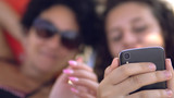 Mother and daughter list gallery of pictures on smartphone during summer holiday, cinematic dof - 220261607