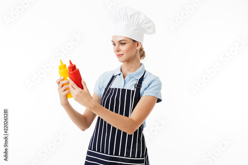 621e6d171c9 Beautiful woman chef in striped apron and white hat dreamily looking on  bottles of ketchup and