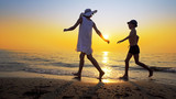 Tourism and travel vacation. Adorable family having fun on beach against sunset. Mother and son walk on beach an play, cinematic steadicam shot - 220279811