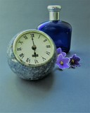 stone clock with perfume bottle and flowers - 220281045
