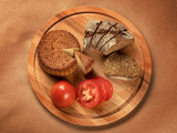 Round cheese, sliced bread and tomatoes on round wooden board top view - 220299287