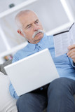 senior man in sofa with laptop computer - 220299686