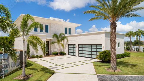 Fototapeta elevated front view of a modern white residential home with palm trees and blue skies