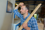 Man holding plank of wood - 220308234