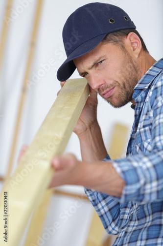 handsome carpenter measuring wood