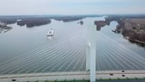 Aerial of a coal barge pushed by tugboat moving up the Mississippi River near Burlington Iowa with suspension bridge foreground. - 220311058