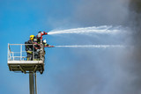 Firefighters extinguish a fire by the top of the building. - 220313274