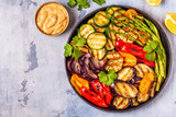 Grilled vegetables on a plate with sauce.