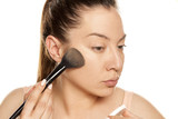 Young woman applying powder foundation with brush on white background - 220355680