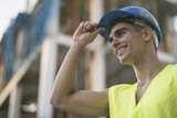Smiling latino or caucasian dark haired construction worker touching his hardhat - 220364417