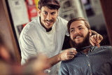 smiling hairdresser shaving with scissors . - 220382255