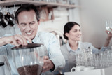 Making coffee. Cheerful confident barista working with a coffee machine and looking glad - 220383472