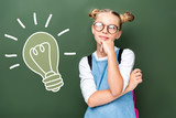 pensive schoolchild in glasses looking up near blackboard with light bulb sign - 220387272