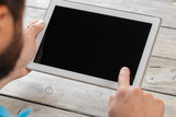 hands of a man holding tablet device over a wooden workspace table - 220389018