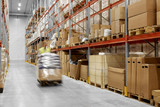 logistic business, shipment and loading concept - worker carrying loader with goods at warehouse