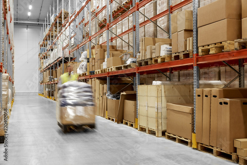 Leinwandbild Motiv logistic business, shipment and loading concept - worker carrying loader with goods at warehouse