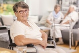 A portrait of a smiling elderly woman in a wheelchair inside a common room of a luxurious care home for seniors. Blurred background. - 220404211