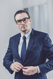 Confidence in himself. Portrait of a handsome presentable man in business clothes and glasses buttoning his jacket while looking at camera - 220404263