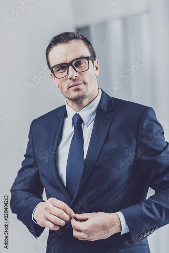 Leinwandbild Motiv Confidence in himself. Portrait of a handsome presentable man in business clothes and glasses buttoning his jacket while looking at camera