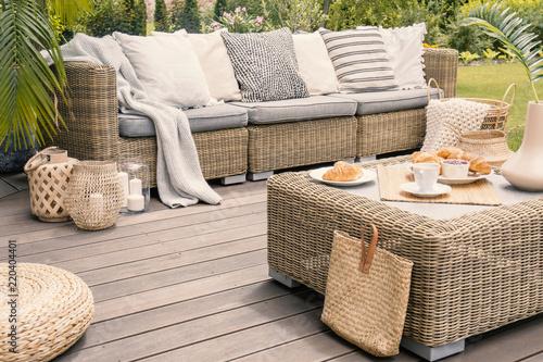 Leinwanddruck Bild Wicker patio set with beige cushions standing on a wooden board deck. Breakfast on a table on a backyard porch.