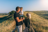 happy young parents looking at adorable little son while standing on rural path - 220412654