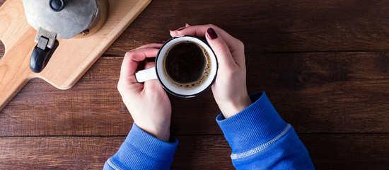 Coffee lover, mug, wooden table, top view, female hands, long banner © yakovlevadaria