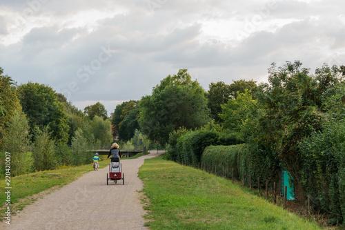 canvas print picture Radfahrerin mit anhänger und Kind