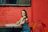 Young girl in summer street vintage cafe with soft drinks . Girl holding a glass - 220423084