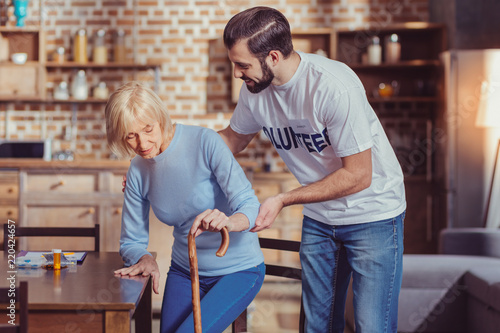 Leinwanddruck Bild Help is here. Reliable unshaken pleasant volunteer standing near a senior woman supporting and helping her.