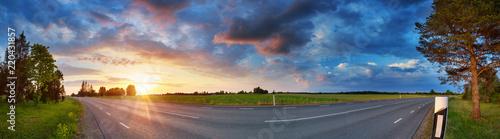 Leinwanddruck Bild black asphalt road and white dividing lines at sunset