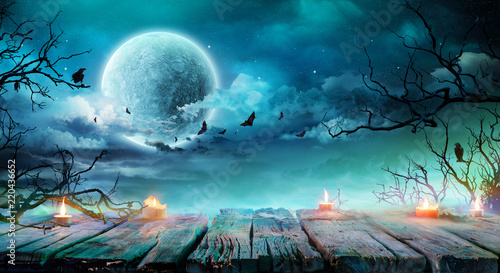 Leinwanddruck Bild Halloween Background  - Old Table With Candles And Branches At Spooky Night With Full Moon