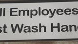 A pan shot of a restroom sign requiring employees to was their hands before returning to work. - 220437216