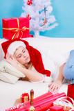 girl wearing santa hat sleeping on sofa at home - 220451623