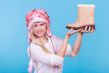 Woman in furry winter hat holding beige boots - 220451632