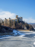 Medieval castle in Niedzica, Poland, in winter at partially frozen artificial Czorsztyn lake on Dunajec river. Sunset light.