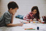 Cute Siblings Drawing Pictures Laying at Floor - 220466027
