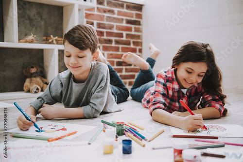 Cute Siblings Drawing Pictures Laying at Floor © VadimGuzhva