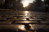 road from paving stones in the rays of the setting sun - 220483073