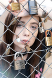 Young girl with green eyes looking through fence - 220493470