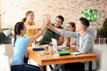 Group of teenagers giving high five indoors