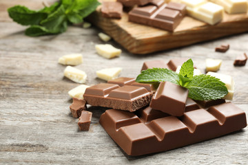 Different kinds of chocolate with mint on wooden table
