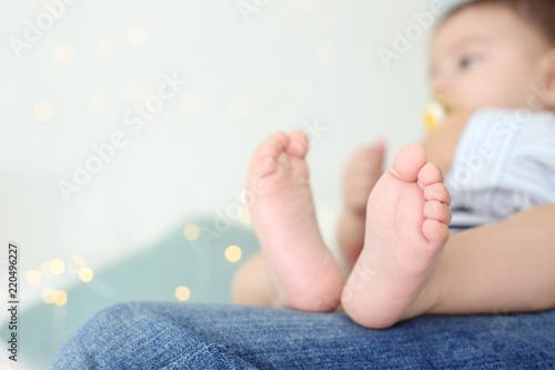 Leinwanddruck Bild Loving mother holding her baby on light background, closeup