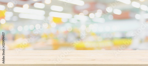 Wood table top with blur grocery store background with bokeh light - 220496437