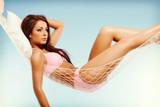 Beautiful woman in bikini relaxing in a hammock in vacation time - 220502249