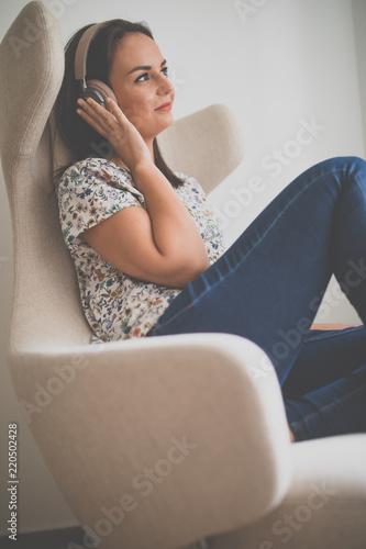 Pretty, młoda kobieta słuchanie jej ulubionej muzyki w hi-fi słuchawki siedzi w designerskim godz