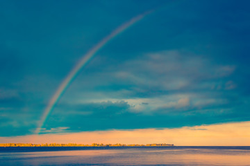 Rainbow over river at sunset. Landscape background © iryna1