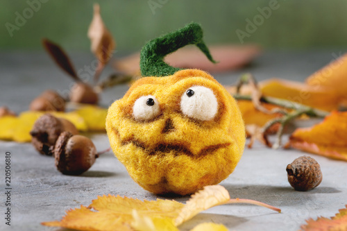 Funny craft Halloween needle felted pumpkin jack o lantern holiday decor with autumn yellow leaves and acorns over grey texture background.